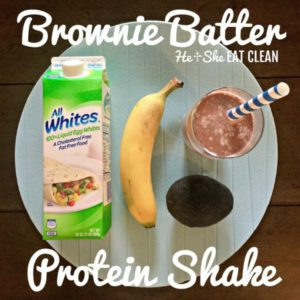 chocolate protein shake in a clear glass with a banana, avocado, and egg white container on the side
