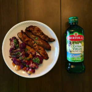 grilled chicken strips next to purple cauliflower with a bottle of olive oil on the side