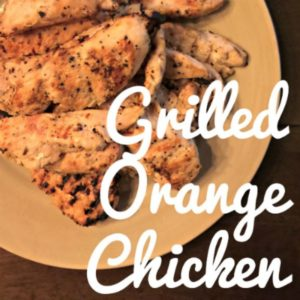 grilled chicken breasts on a beige plate and wooden table with text that reads grilled orange chicken square image