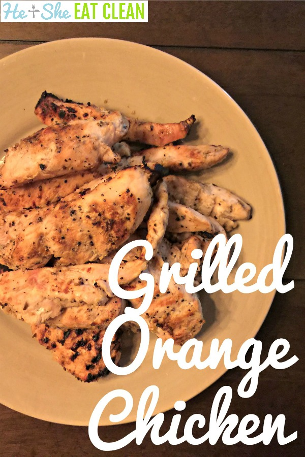 grilled chicken breasts on a beige plate and wooden table with text that reads grilled orange chicken