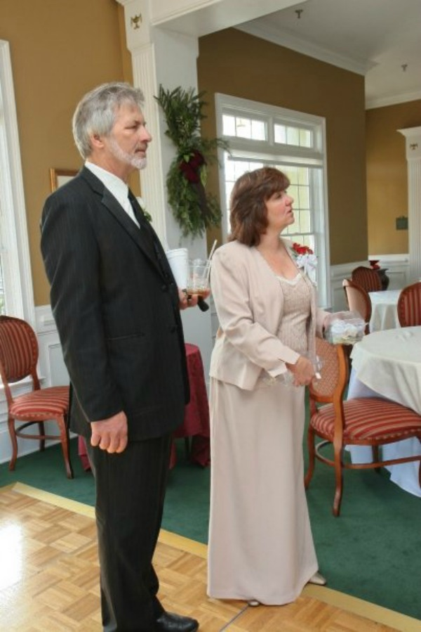 man in a suit and woman in a beige dress standing next to each other