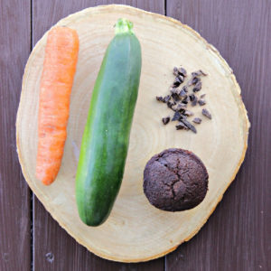 overhead shot of a Chocolate Garden Lites muffin, chocolate chunks, zucchini, and a carrot