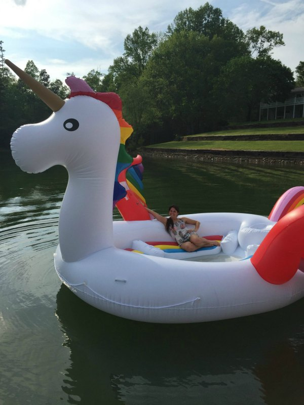 huge unicorn float in a lake with female sitting on it