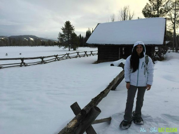 female standing next to a fence in the snow with snowshoes on