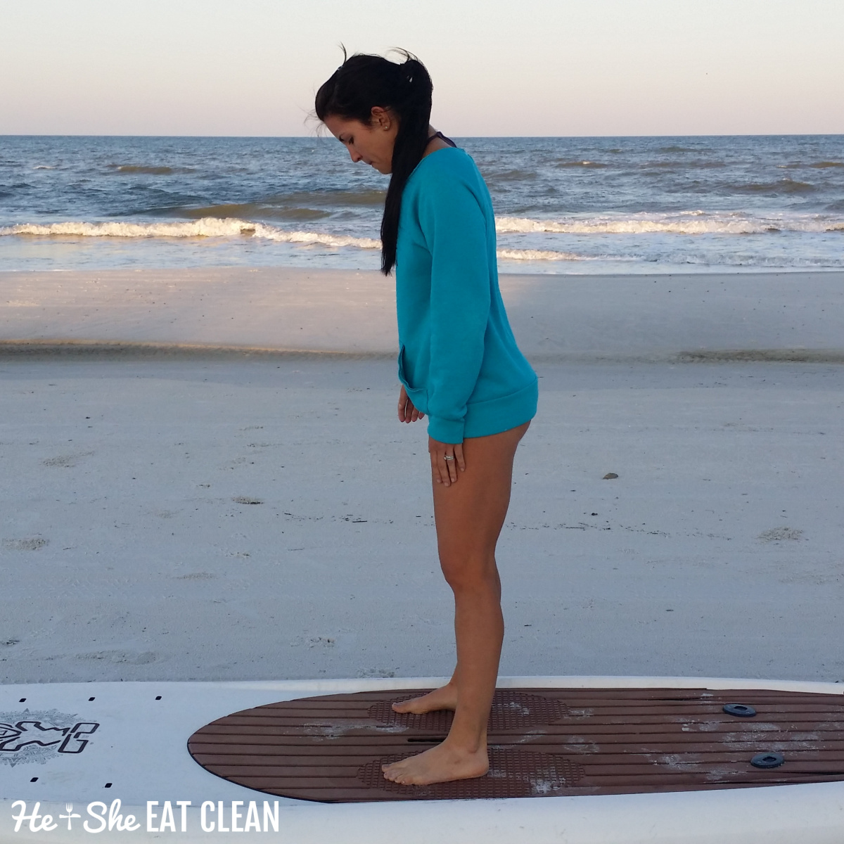 female on the beach standing on a paddleboard wearing a blue sweatshirt