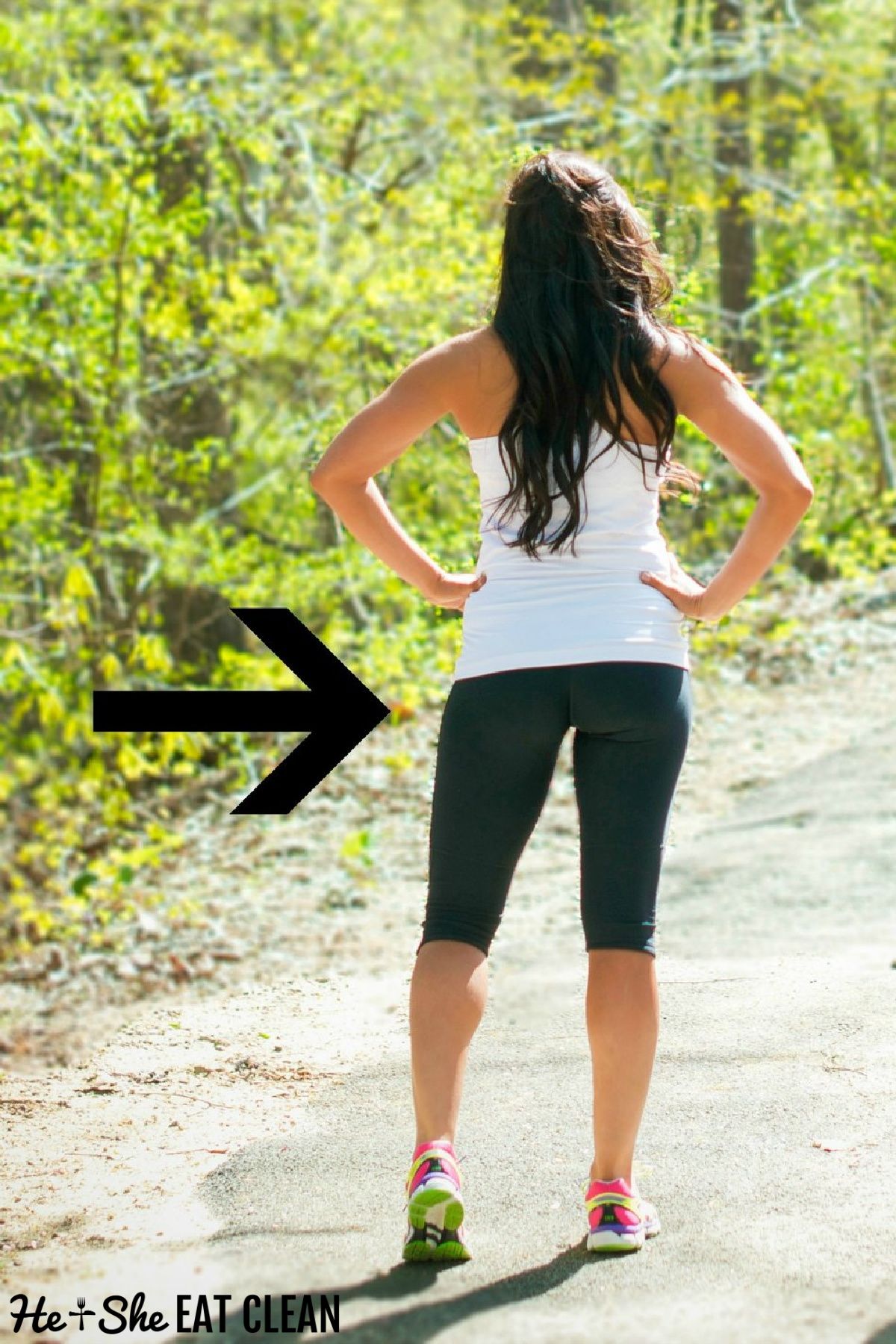 rear image of a female with her hand on her hips wearing a white tank and black workout capris
