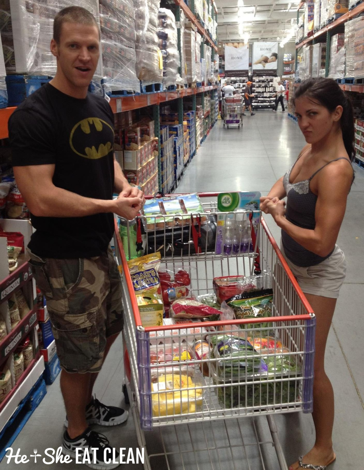 male and female standing next to a grocery cart flexing their muscles