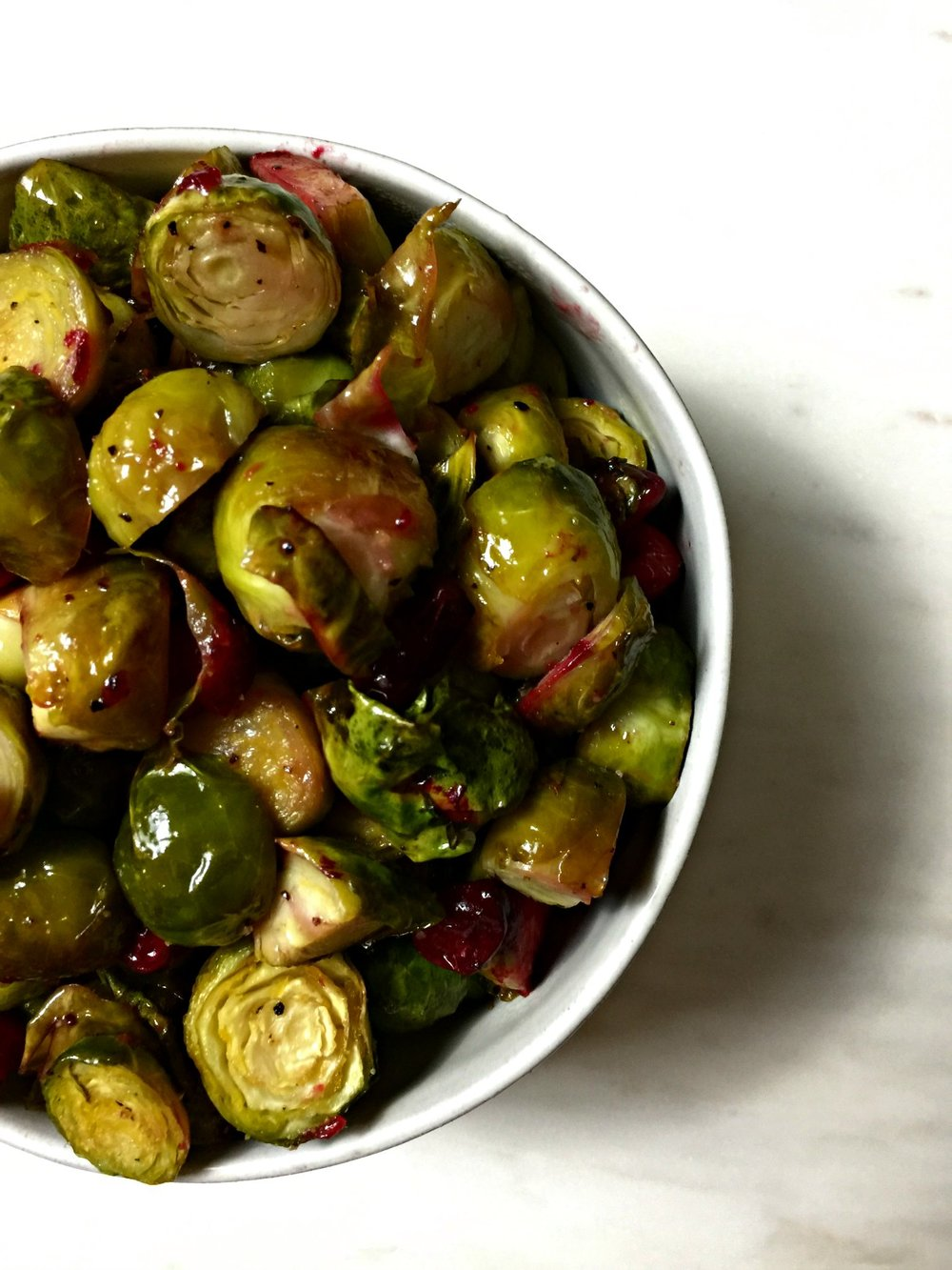 brussels sprouts with cranberries in a white bowl on a white marble surface