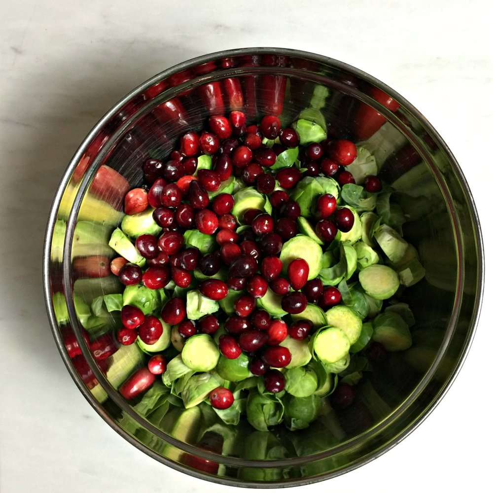 brussels sprouts with cranberries in a stainless steel bowl on a white marble surface