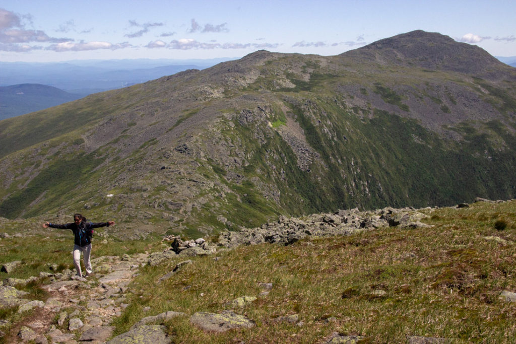 traverse of the White Mountains in New Hampshire with a female hiking up a trail with her arms out