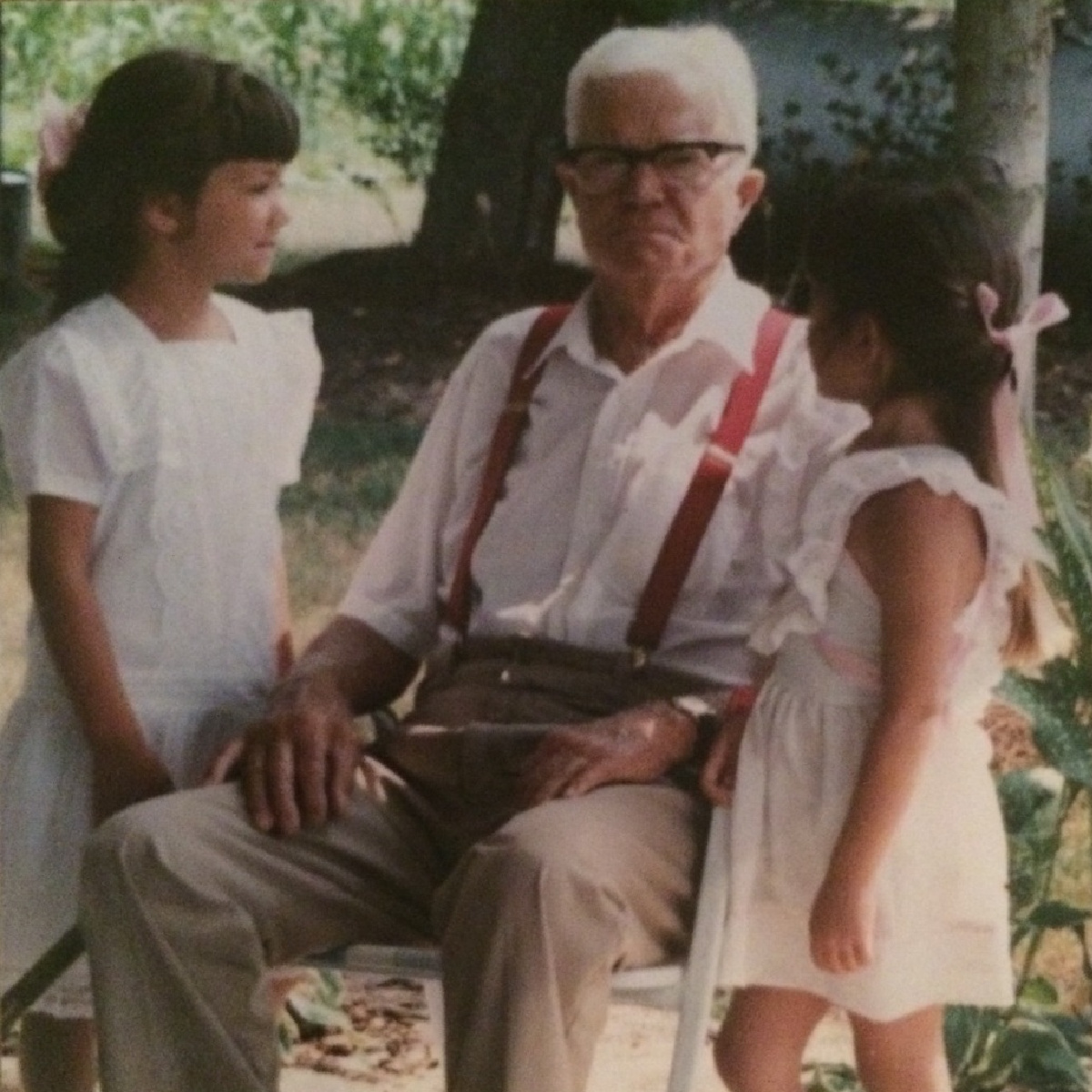 two young girls standing next to a sitting grandfather