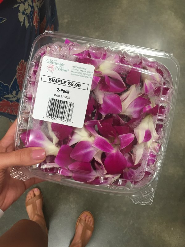female holding a package of 2 pink leis from Costco in Hawaii