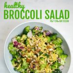 broccoli salad topped with cheddar cheese and pecans in a white bowl on a white marble top square image