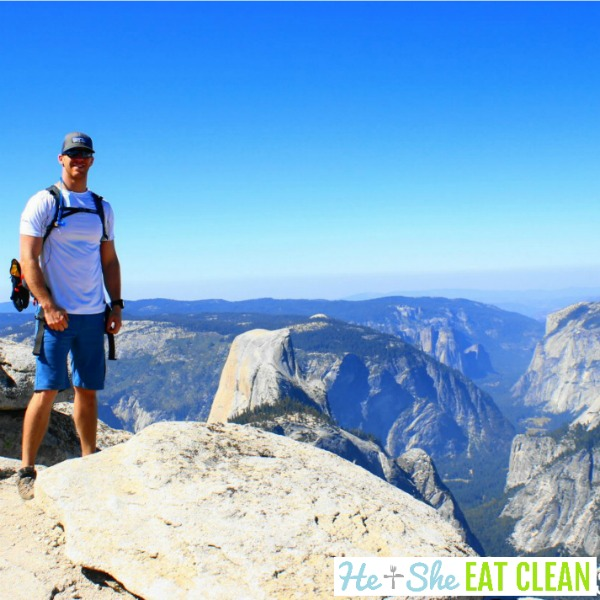 male standing on Clouds Rest in front of Half Dome in Yosemite National Park