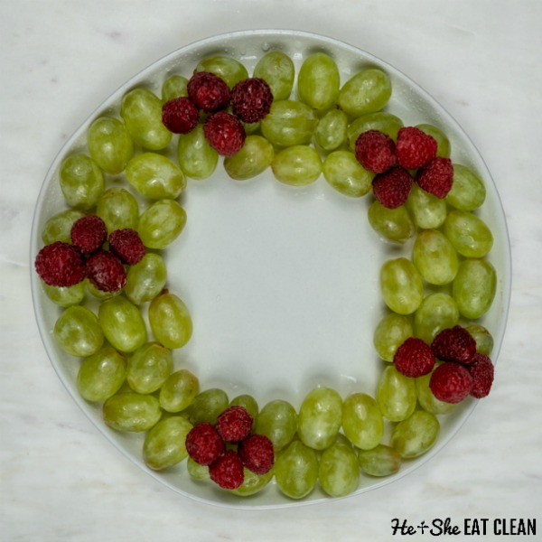 green grapes and raspberries arranges in a wreath on a white plate