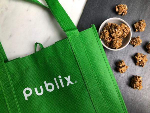 green Publix bag with granola bites next to it on a slate board