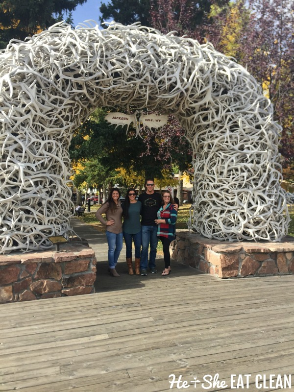 3 females and 1 male standing under the antler arch in Jackson, Wyoming