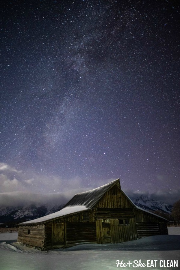 snow covered barn in front of a mountain range - Grand Teton National Park with stars in the sky