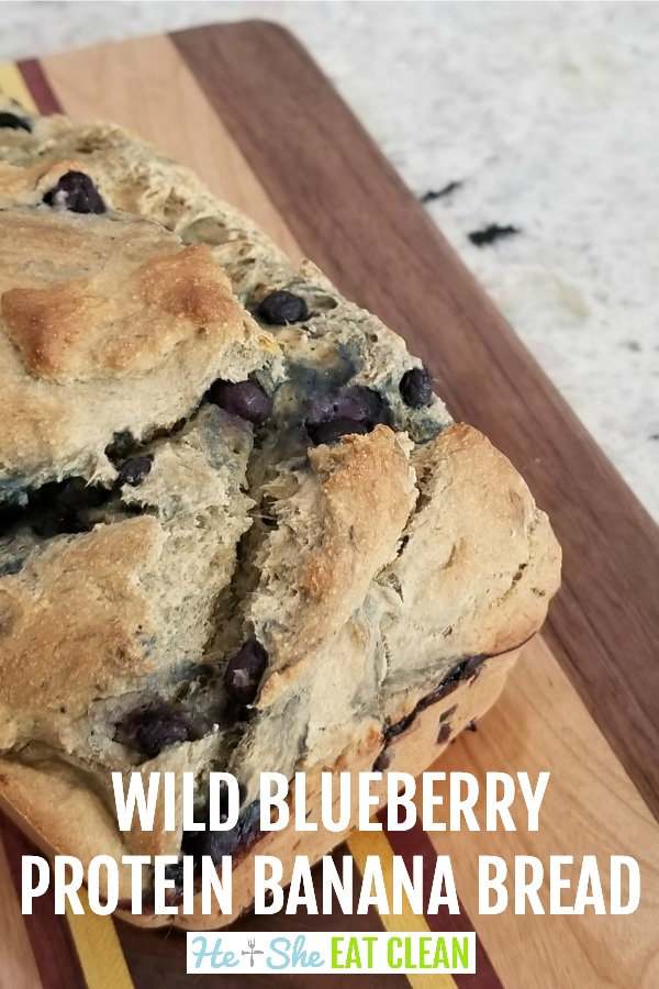 loaf of blueberry banana bread on a wooden cutting board