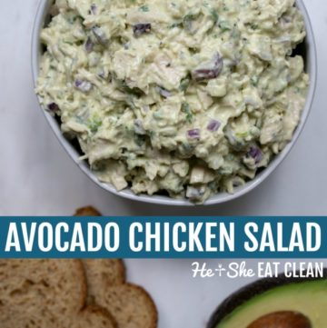 bowl of avocado chicken salad with toast and avocado below on a white marble slab