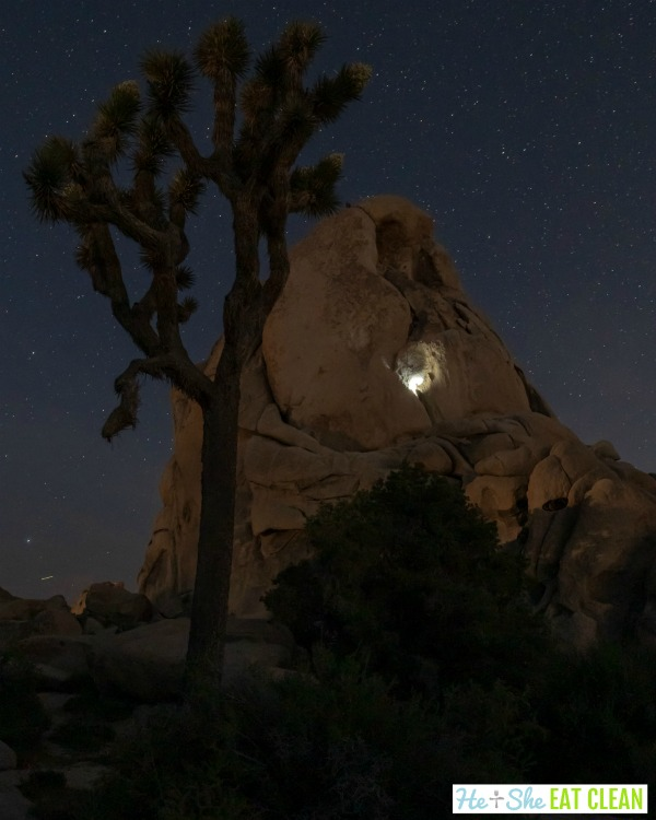 rock mountain with climber using light with night sky and joshua tree