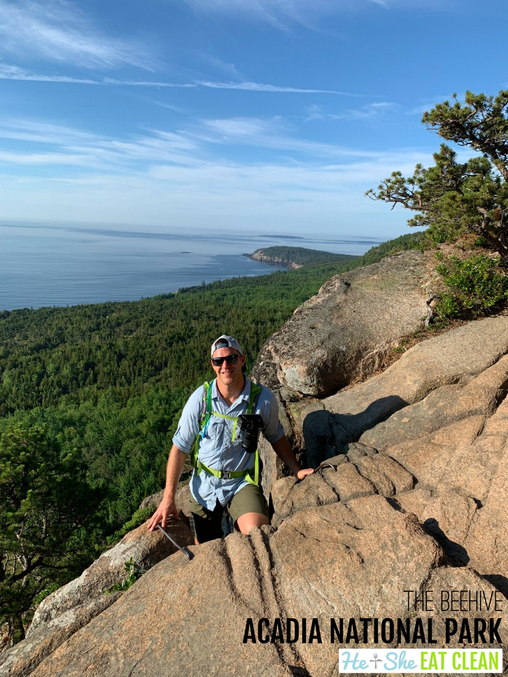 male hiker on the Beehive trail in Acadia National Park in Maine with the ocean and trees in the background