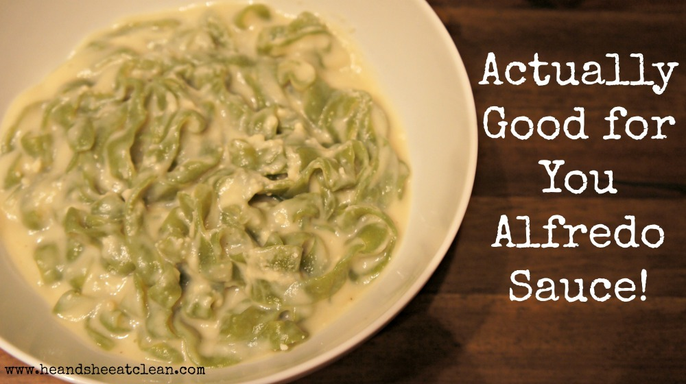white bowl of alfredo sauce with fettuccine noodles on a wooden table