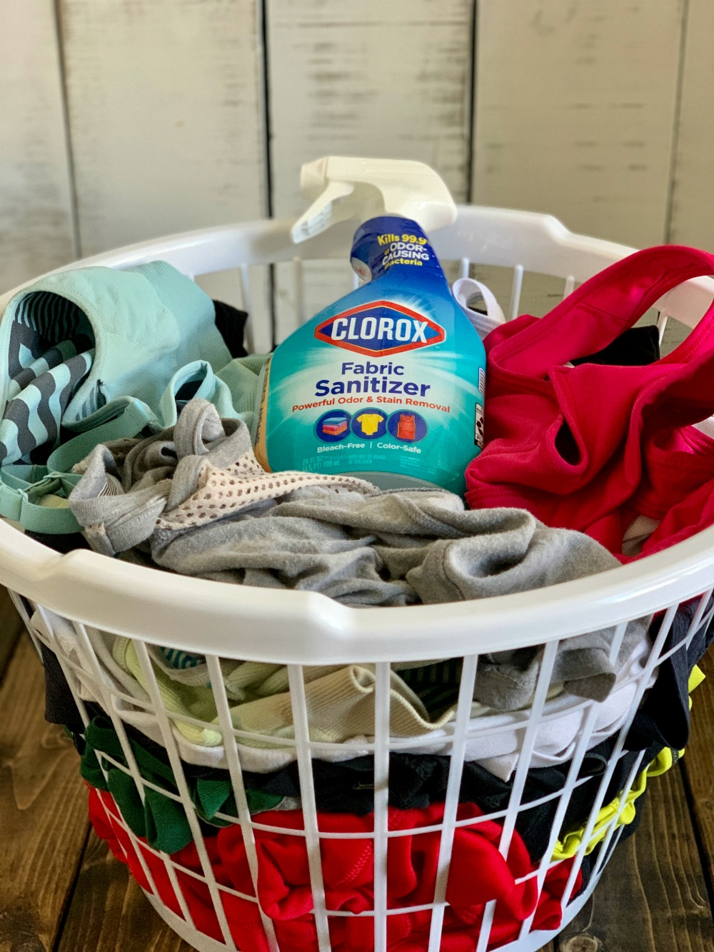 white laundry basket full of dirty clothes and Clorox Fabric Sanitizer