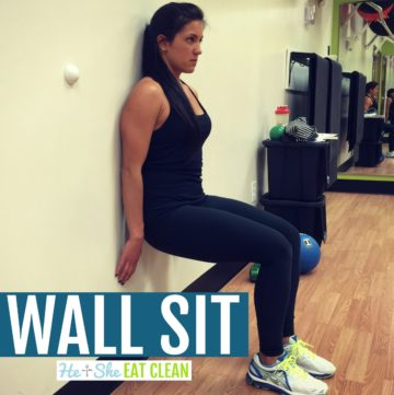 female dressed in black doing a wall sit against a gym wall