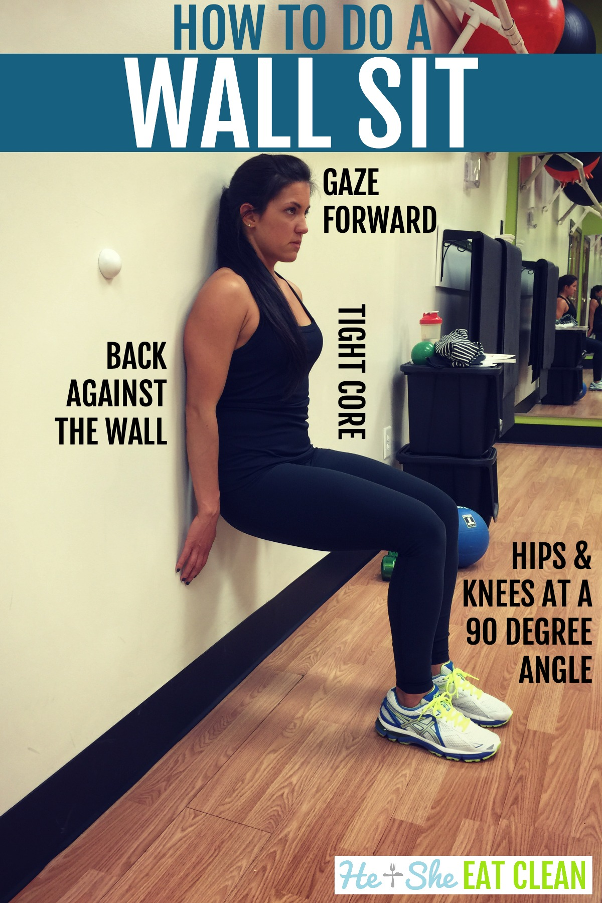 female doing a wall sit against the gym wall