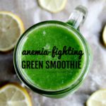 green smoothie in a clear glass jar with cut lemons