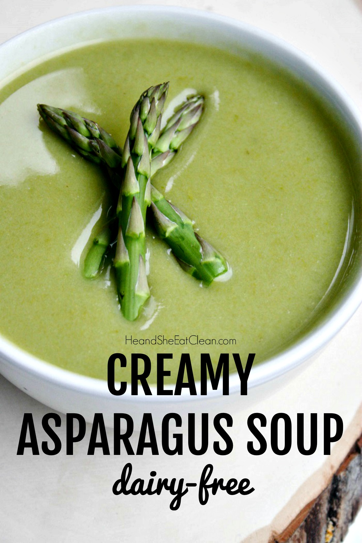 asparagus soup in a white bowl topped with asparagus spears