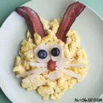 scrambled eggs made to look like a bunny with bacon ears and cheese eyes and whiskers