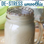 smoothie in a glass major jar with bananas in the background text reads de-stress smoothie