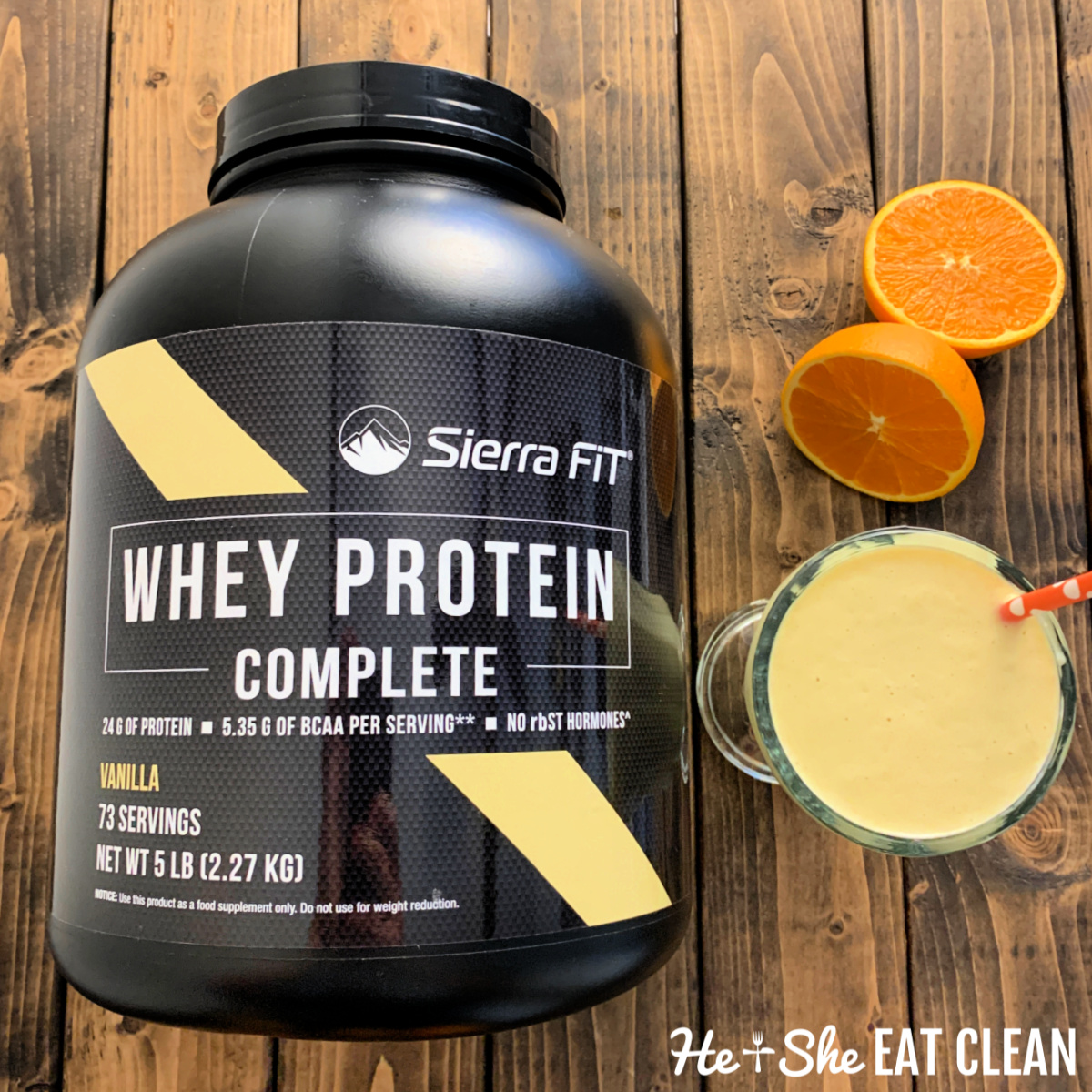 large container of protein powder next to a protein shake and a sliced orange