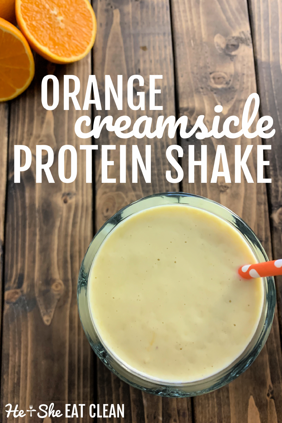 overhead view of protein shake in glass far with orange straw and a sliced orange in the background