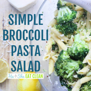 pasta salad with broccoli in a bowl with lemon and cheese on the side