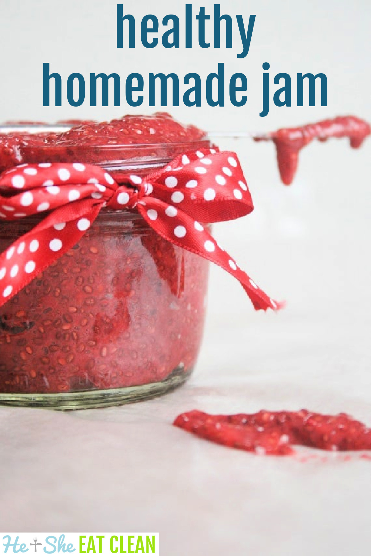 glass jar of red jam with red polka dot bow and a knife across the top of the jar and jam on the table underneath the knife