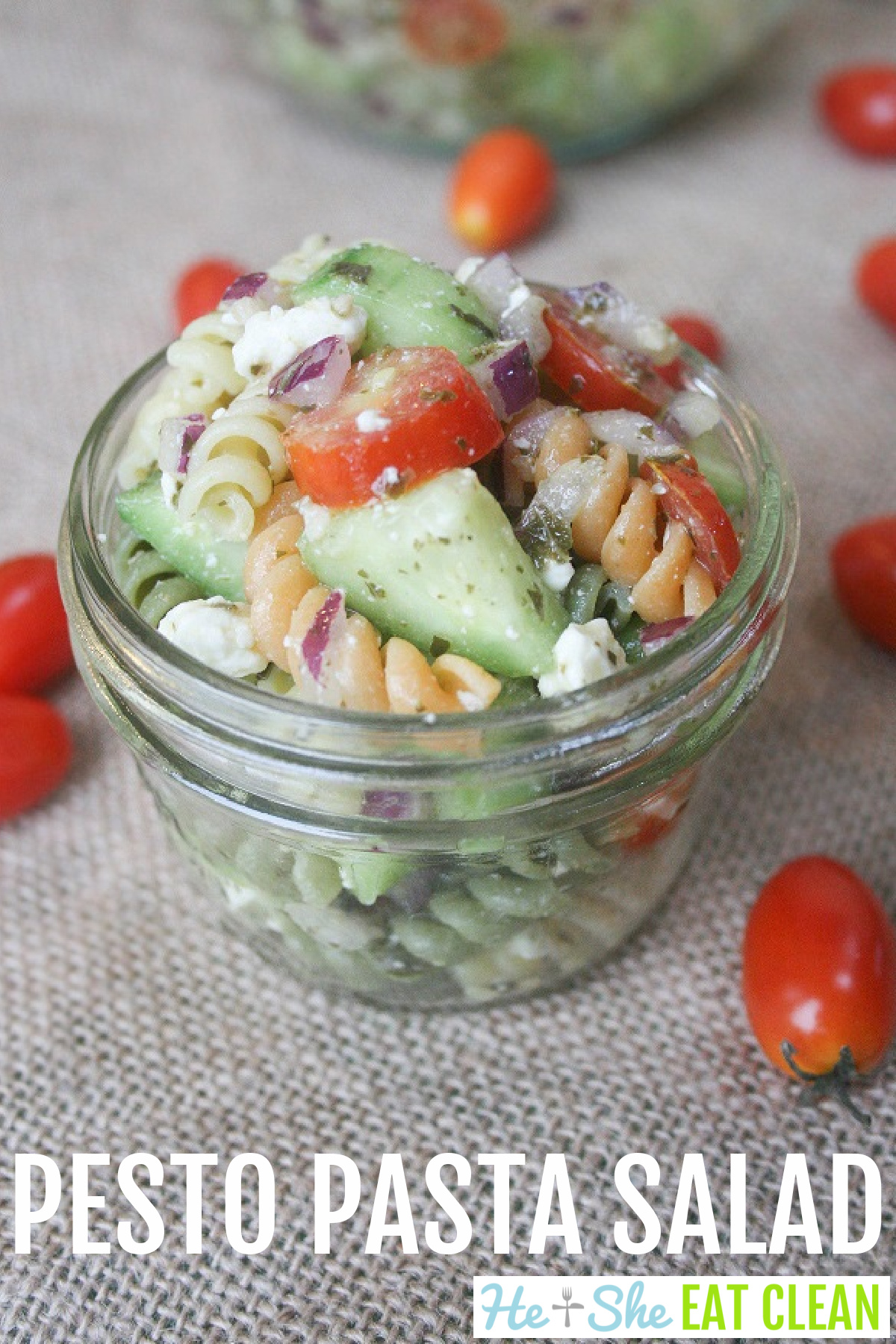 clear mason jar of pasta salad consisting of pasta, cucumbers, tomatoes, red onion, and feta cheese